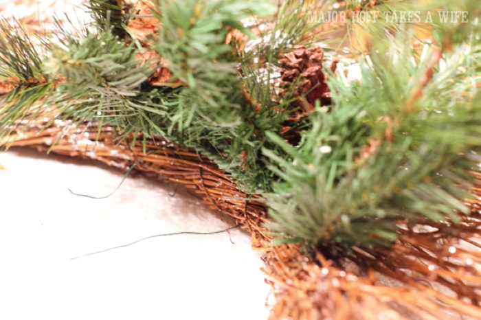 Use floral wire to secure greenery to wreath. World Market inspired wreath. A fun twist on a Christmas wreath. Make a winter wreath that will last all season long and well past. This cute grapevine wreath is adorned with a tiny bird, pinecones, greenery and pom poms. You won't believe how cheap and easy this was to make! And so simple! #Christmas #winter #holiday #wreath #nature #knockoff