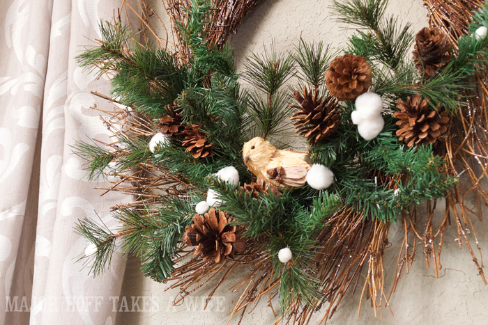Winter Wonderland Nature inspired Wreath. World Market inspired wreath. A fun twist on a Christmas wreath. Make a winter wreath that will last all season long and well past. This cute grapevine wreath is adorned with a tiny bird, pinecones, greenery and pom poms. You won't believe how cheap and easy this was to make! And so simple! #Christmas #winter #holiday #wreath #nature #knockoff