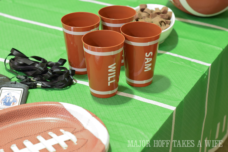 Personalized football cups. Looking for a fun party for your teenage boy? Why not throw a Football video game party? Easy ideas for how to entertain kiddos during the Big Game. Features DiGiorno pizza, personalized football cups, free printable lanyards, and an incredible recipe for football shaped ice cream sandwiches! #GameTimeMVP #CollectiveBias #ad