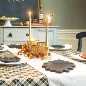 Plaid tablecloth, white dishes, and fall accents on a Thanksgiving tablescape