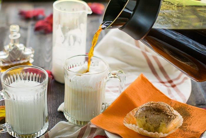 pouring coffee over milk for latte macchiato