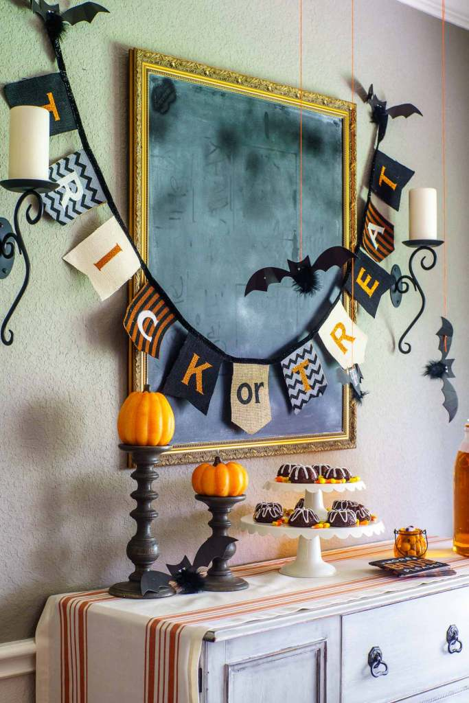 Halloween buffet display with pumpkin candles, gingerbread mini bundt cakes, and a trick or treat banner.