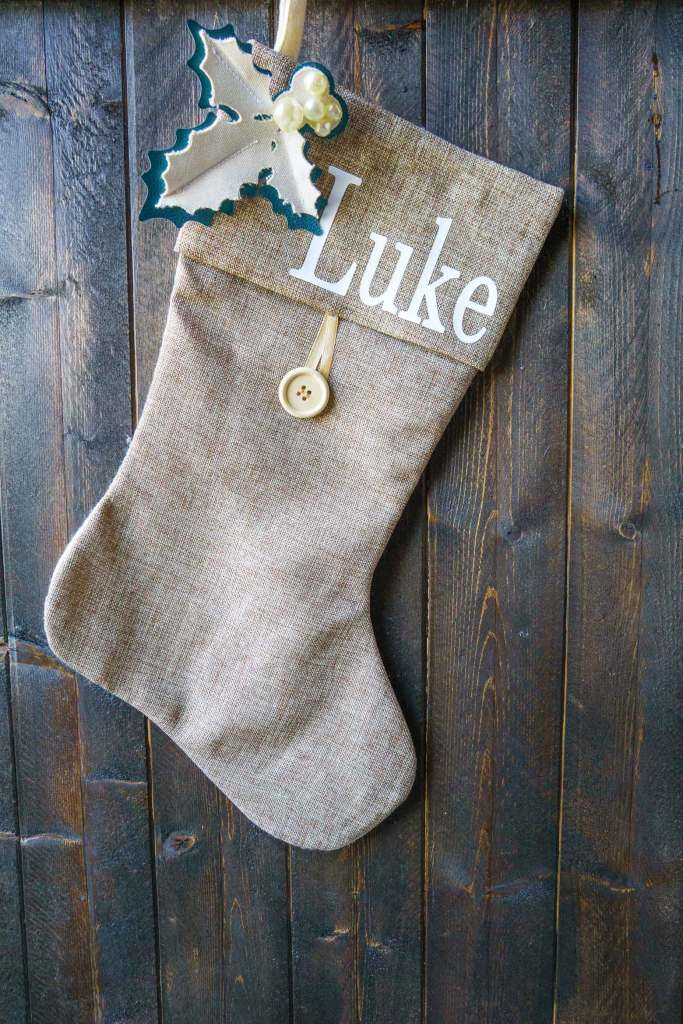 Level up a store bought stocking with homemade holly from leather and canvas on a Cricut machine. Add fonts to make it a personalized Christmas stocking!