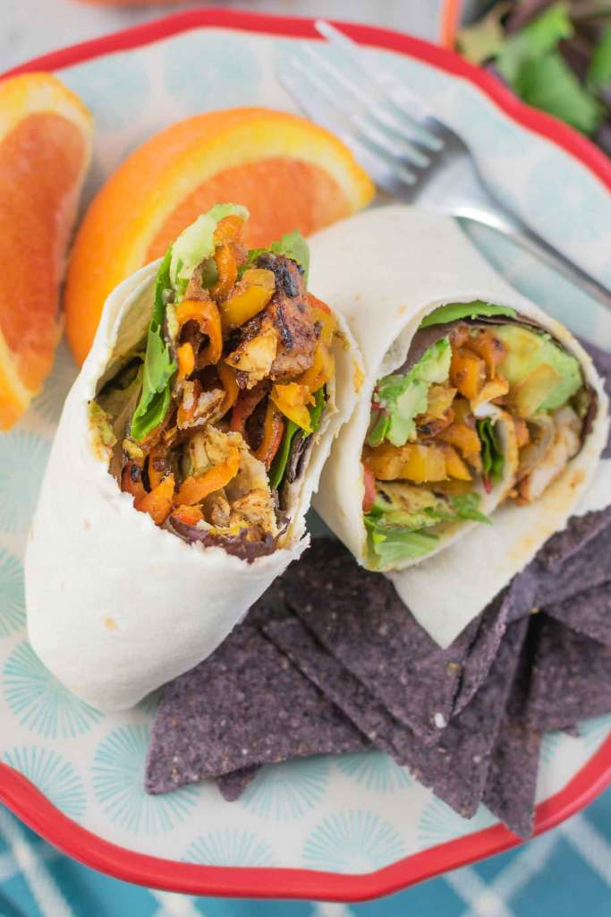 grilled chicken strips, avocado, bacon and veggies in a wrap on a plate with blue chips
