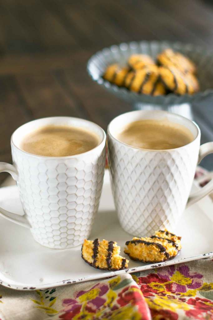 Vanilla caramel mocha lattes in white latte cups on a white tray with chocolate coconut cookies