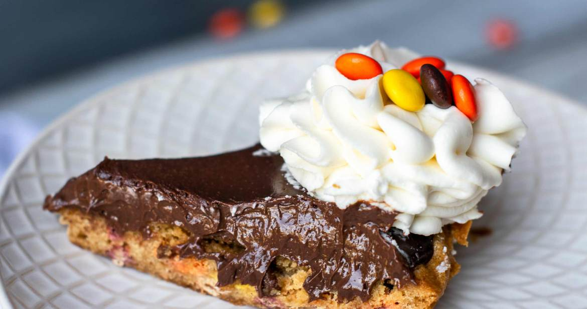 A slice of delicious Reese's pie with chocolate ganache and peanut butter cookie crust!
