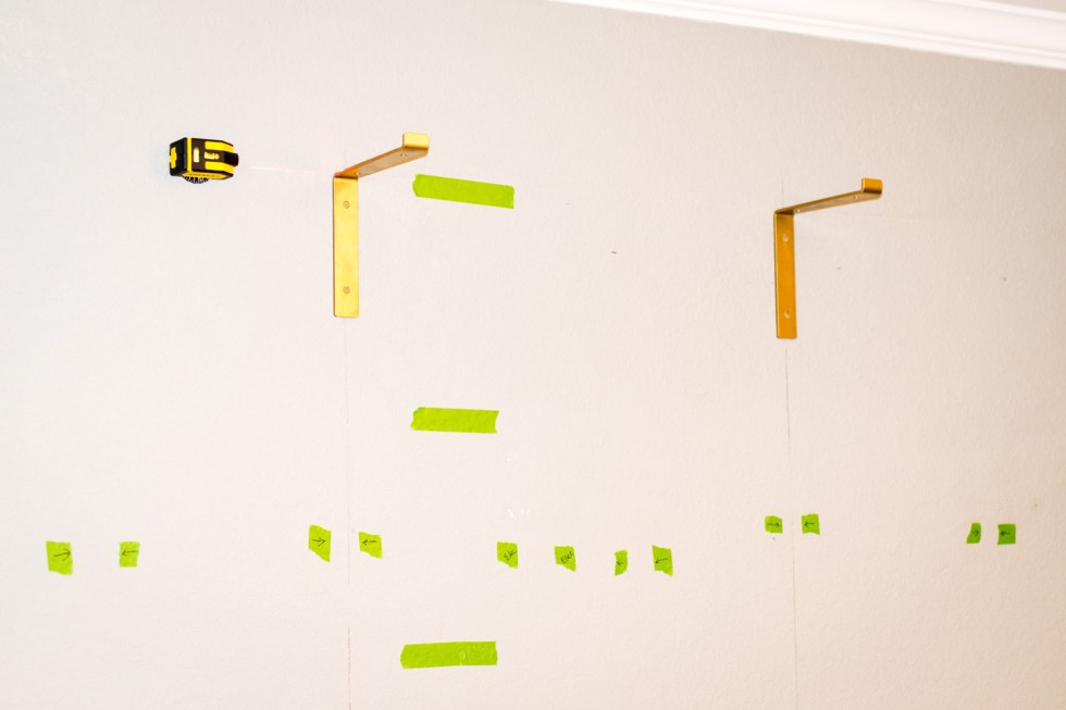 installing shelf brackets by finding studs in the wall and using a laser level