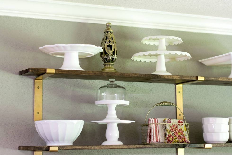 Cake stands and other white dishes on breakfast room open shelves