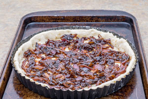 layering caramelised onions onto a tart shell