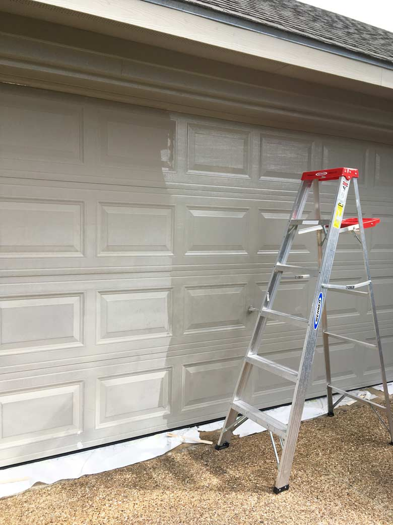 painting a garage door with a roller