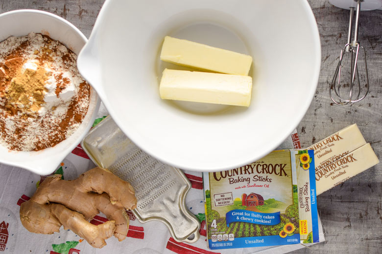 the start of gingerbread cookie dough requires fresh ginger, flour and spices and butter in a bowl