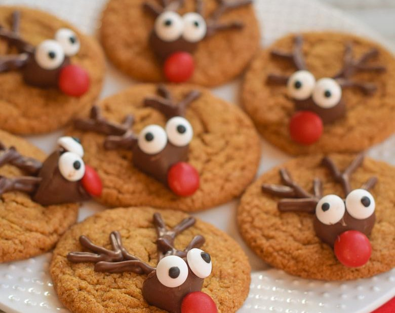 Gingerbread reindeer cookies on a white plate with faces made from chocolate kiss candy, candy eyes and a candy nose.
