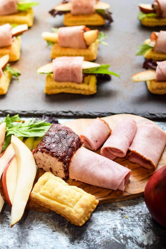 goat cheese appetizers are easy to assemble with puff pastries, meats, fruit and a log of goat cheese on a cutting board