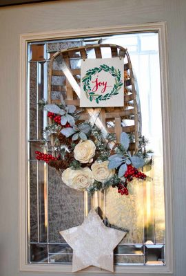 A winter wreath made from white roses, evergreens, berries and more on a tobacco basket hanging on a door.