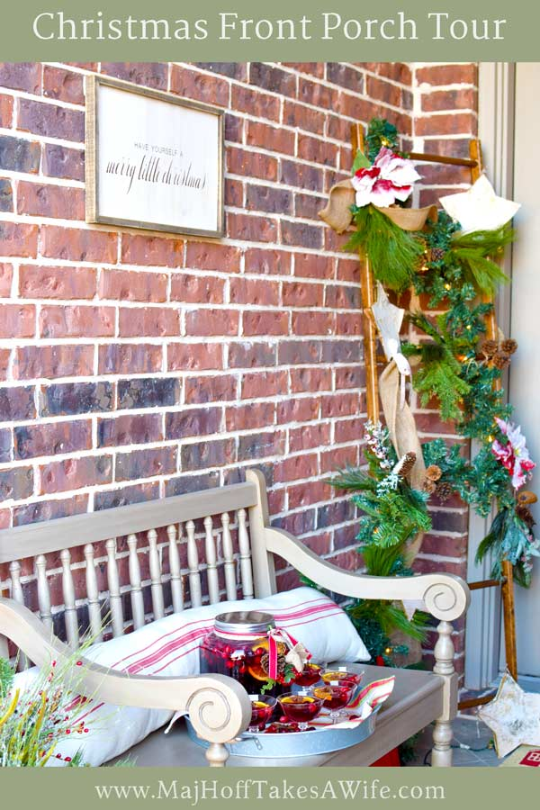 This Christmas porch is full of holiday cheer! Enjoy the farmhouse style decor and grab lots of ideas for a simple Christmas wreath, a ladder with lights and garland, a bench with an inviting drink, and lots of other DIY decorations. Be sure to check out all the details!