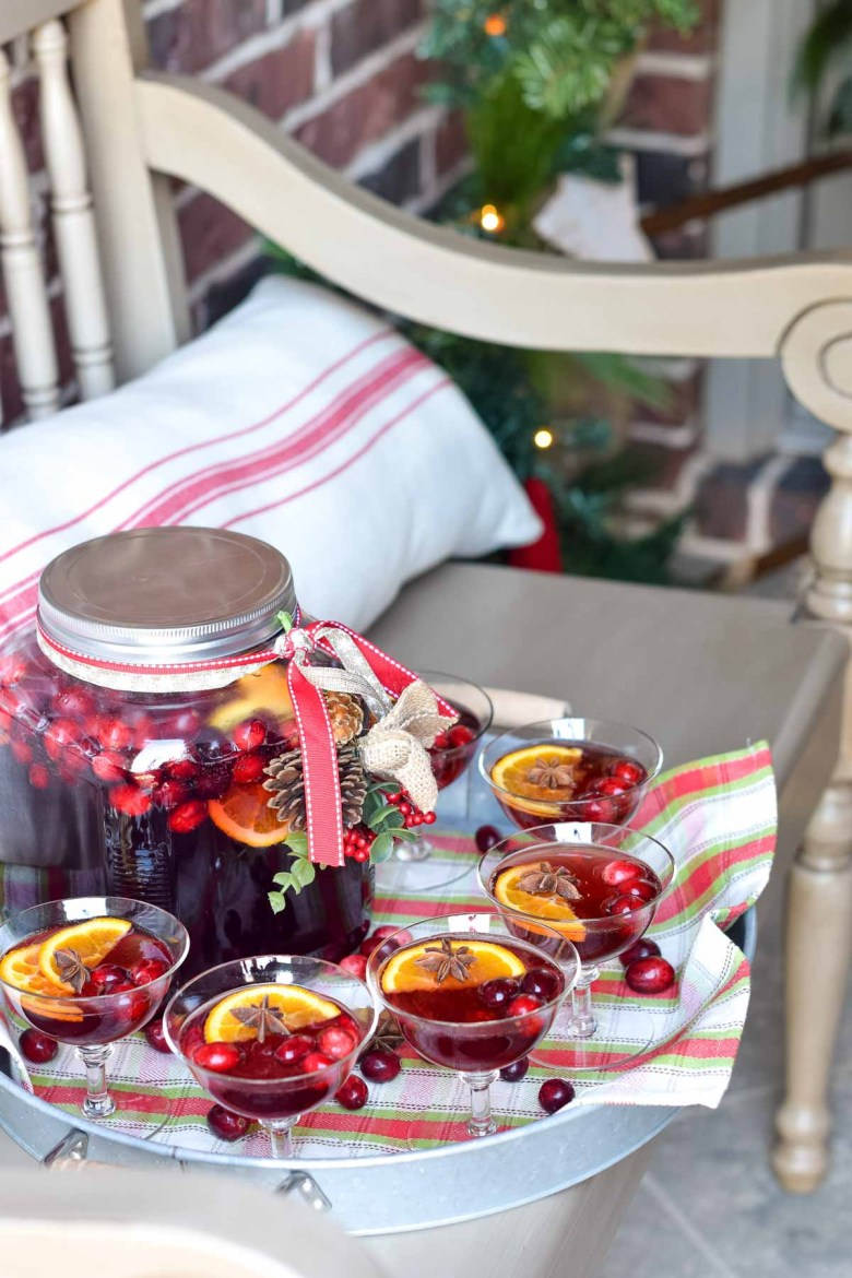 A front porch decked out for Christmas with a cranberry punch to greet guests on a tray