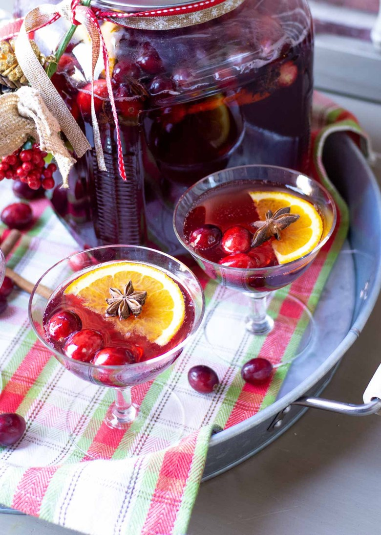 Garnish a cranberry cocktail with fresh cranberries, star anise and orange slices