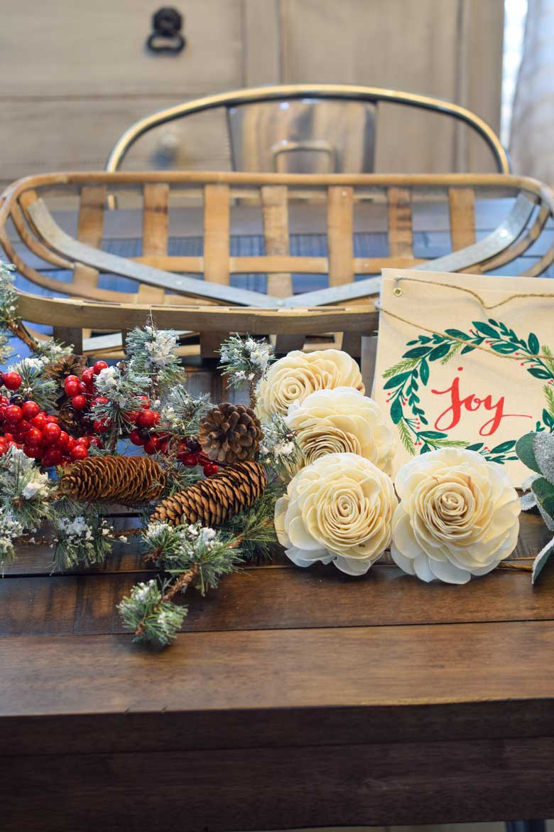 Supplies needed for a winter front door wreath includes rose stems, evergreen floral picks with berries, a tobacco basket, and more