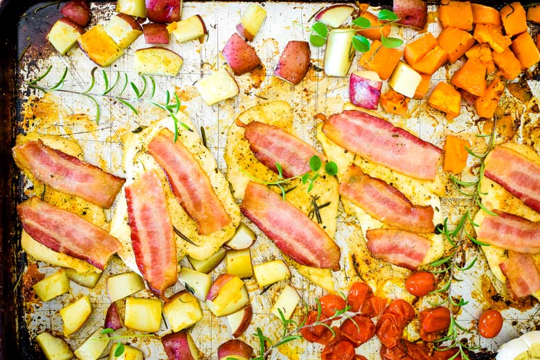 sheet pan full of veggies and chicken with bacon slices