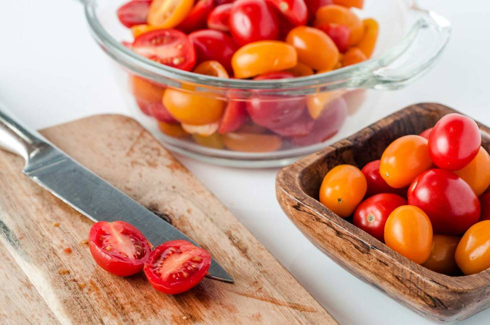 fresh cherry tomatoes being sliced for a homemade pasta sauce