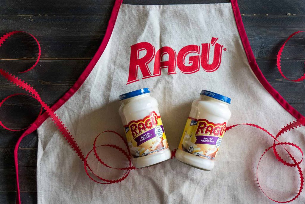 RAGÚ® butter parmesan sauce jars on an apron