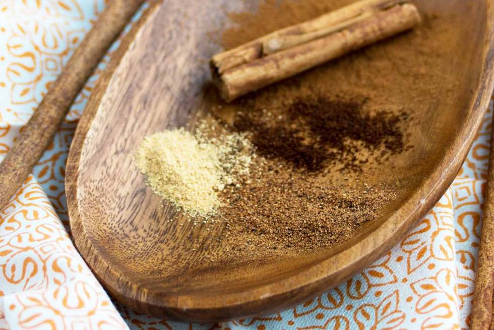 cinnamon, cloves, ginger and nutmeg on a wooden tray
