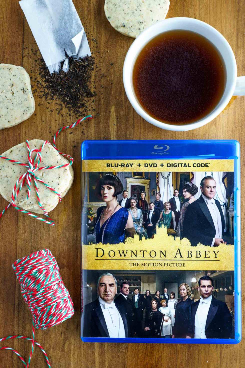 Downton Abbey DVD flat lay with teacup, loose tea and biscuits
