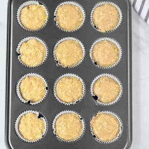 muffin batter in a gray muffin tin