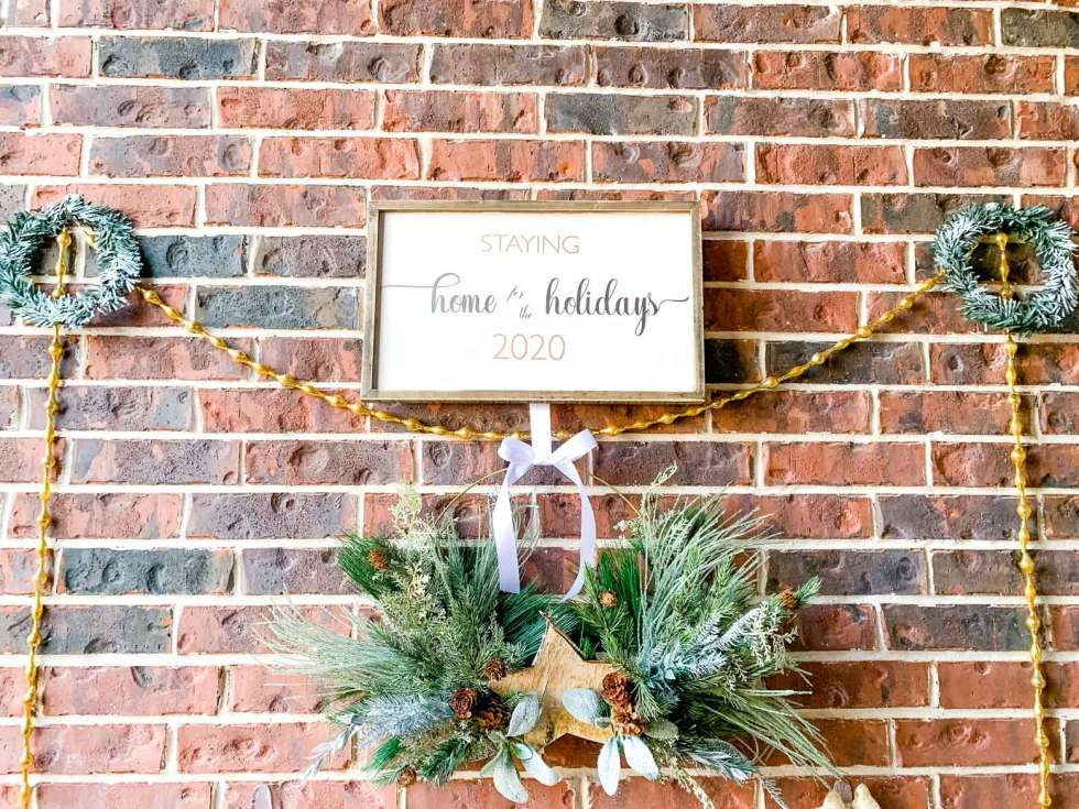 two small green wreaths and gold garland flank a holiday sign