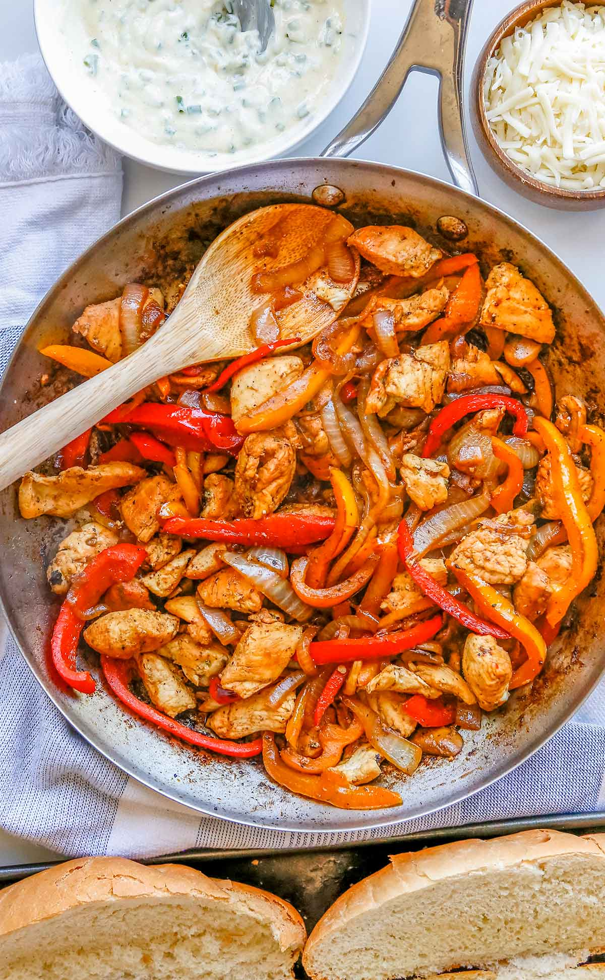 a skillet of cooked pieces of chicken breast  with peppers, onions, and mushrooms.