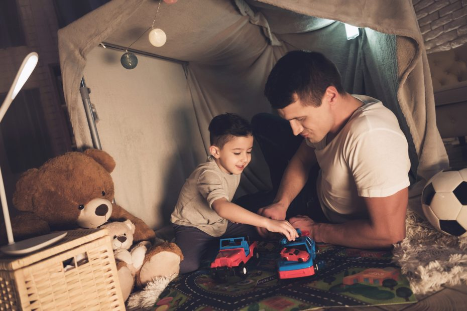Father and son playing with cars in a blanket fort at night