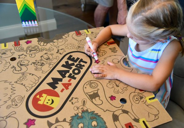 Young girl coloring a Make-A-Fort panel