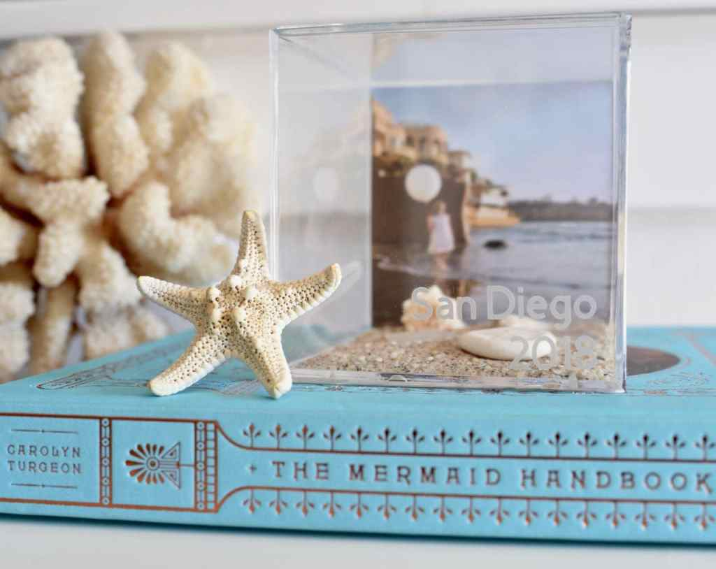 DIY vacation memory cube tutorial. Preserve those memories with a clear vacation memory box! Just add photos and mementos from vacation to a clear acrylic box, then add the date and destination onto the front with etch vinyl!