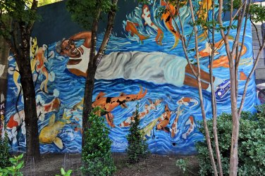 """""""Fish Are Jumping and the Cotton is High"""" mural by Ashely Dopson at the entrance to the Krog tunnel. This mural depicts long-time Cabbagetown resident, Bertha floating in one of David Thayer's koi ponds."""