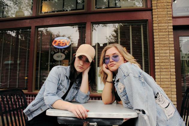 two women in gray chambray jackets sits at table