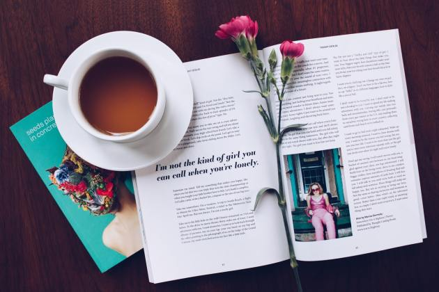 cup and book and rose on a table