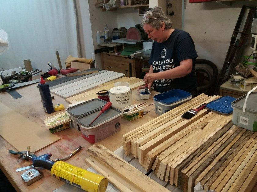 Sue paints pieces of pallet wood various colours