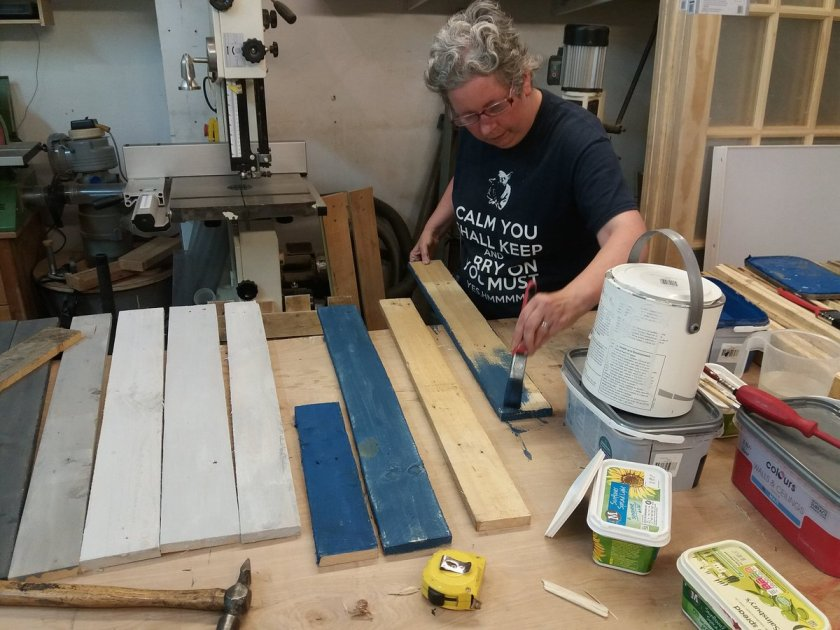 Sue paints strips of pallet wood with blue paint