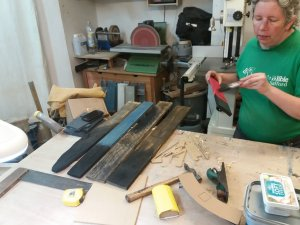 Sue paints a charred effect on pieces of pallet wood