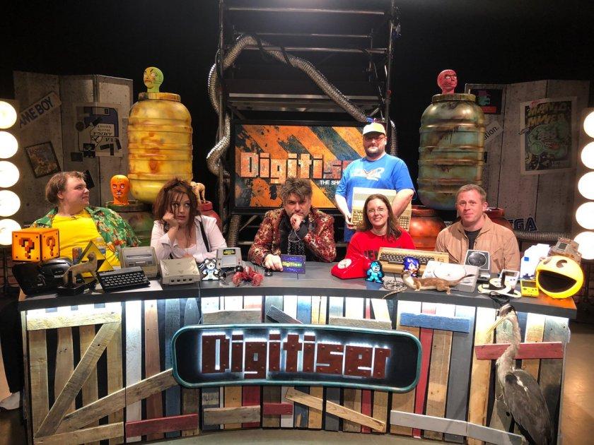 The cast of Digitiser sit behind the desk on set