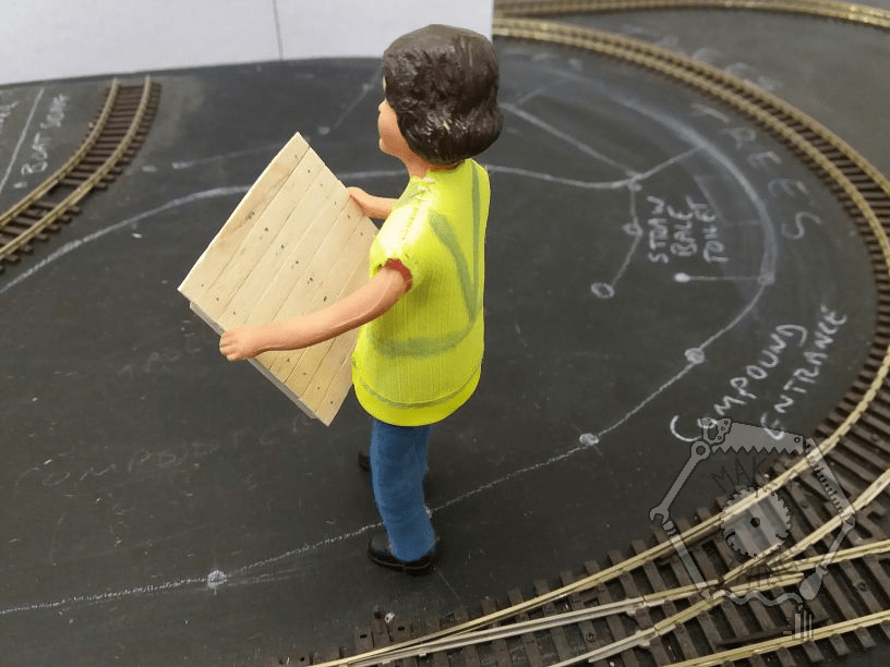 arriet is carrying the platform and walking across the tarmac in the garden railway. There is rail track laid on the ground, with chalked writing and a white wall structure in the back ground.