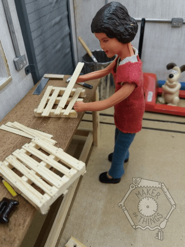 Harriet is standing at her bench assembling a second miniature pallet. A completed one is on the bench next to her.