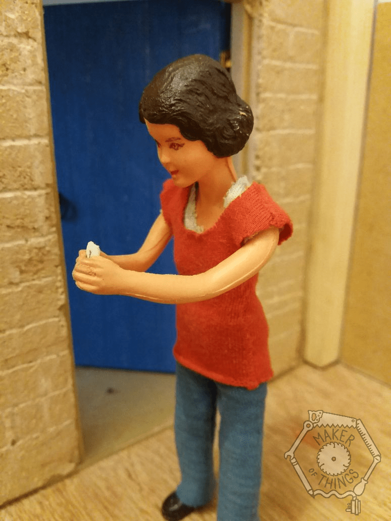 Harriet is standing outside her workshop with a small envelope in her hands.