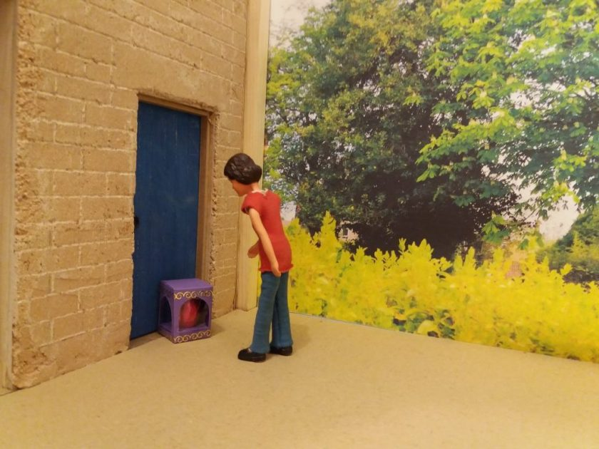Harriet is outside her workshop looking at a purple box outside the workshop door.