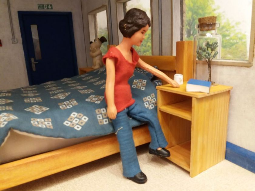 Harriet is sitting on the edge of her bed and pointing at the bedside cabinet