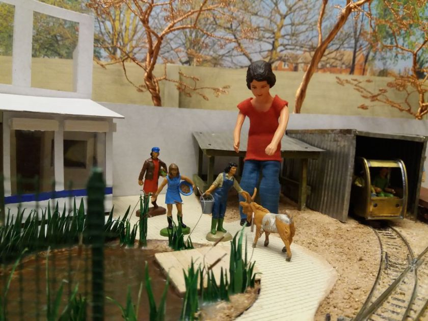 Harriet is in the garden railway indicting three of the human figures and a goat figure next to the pond.