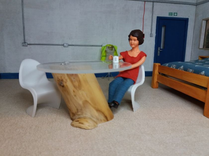 Harriet is sitting in her bedsit at a round glass table. The base of the table is a large skewed log. There are two white Panton chairs, Harriet is sitting on one.