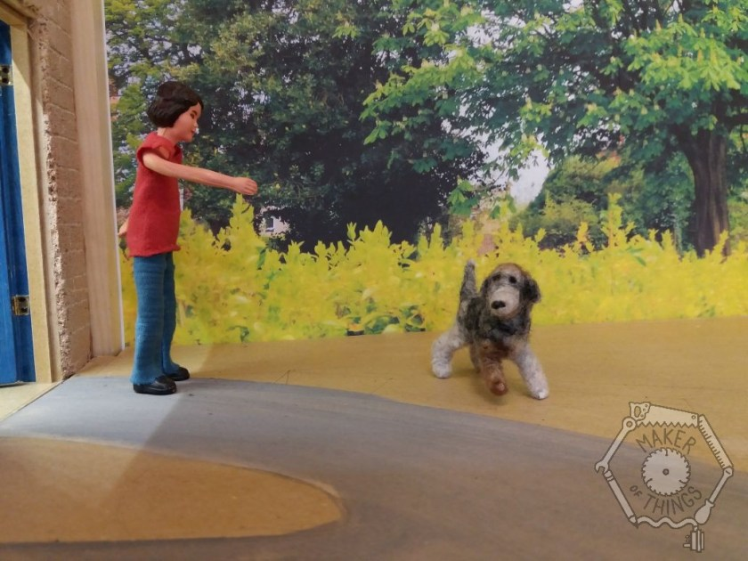 Harriet is pointing away from her workshop. The dog is reluctantly turning to leave.