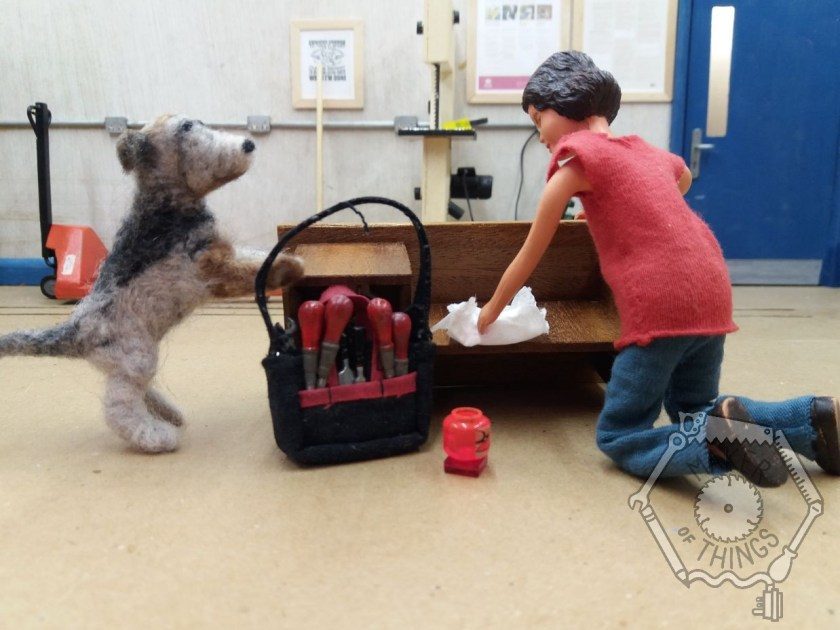 Harriet has the bench on its side in the workshop. She has her tool bag with her and is cleaning the underside of the bench with a cloth and tub of polish. Monty has his paws on the bench looking.