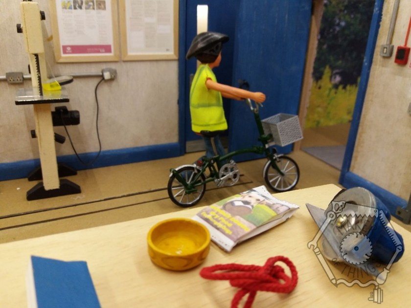 Harriet is pushing her bicycle back out of the workshop. She is wearing hi-vis and her bicycle helmet. The bag of dog food, bowl and lead are on the plywood board with her tools.
